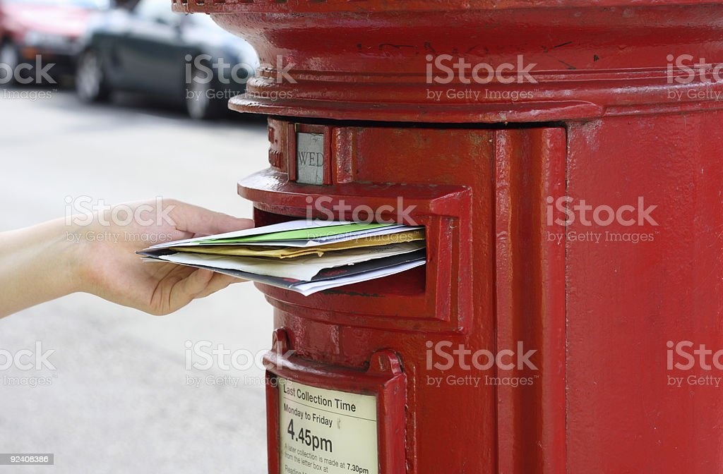 girls hand posting letters to red british postbox on street royalty-free stock photo
