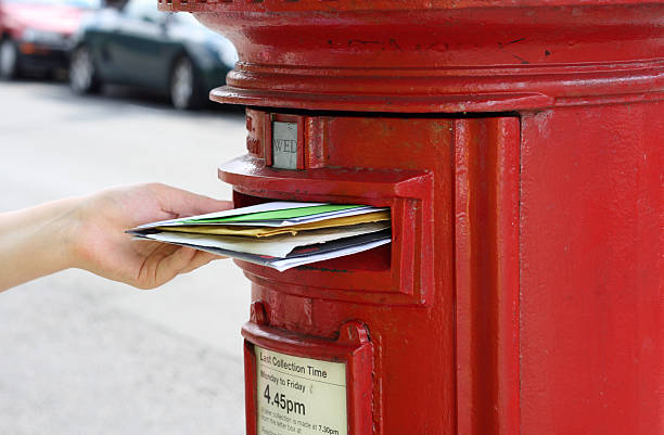 girls hand posting letters to red british postbox on street stock photo