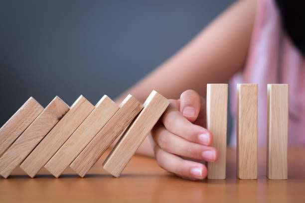 Girl's hand Stopping Falling wooden Dominoes effect from continuous toppled or risk. Girl's hand Stopping Falling wooden Dominoes effect from continuous toppled or risk, strategy and successful intervention concept for business and education. boundary stock pictures, royalty-free photos & images