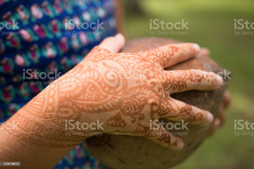 Girls Hand With Temporary Henna Tattoo Holds A Coconut Stock Photo