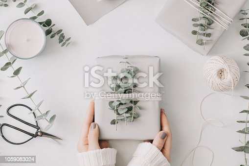istock Girl's hands hold a gift box with minimalist style wrapping design. The concept of celebration events and wrapping gifts. Flat lay, top view. 1059083024