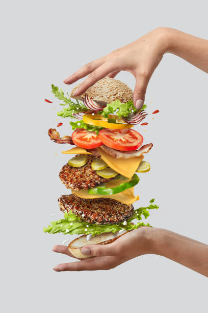 Girl's hands hold big tasty homemade burger with flying natutal ingredients on a white background. Copy space. stock photo