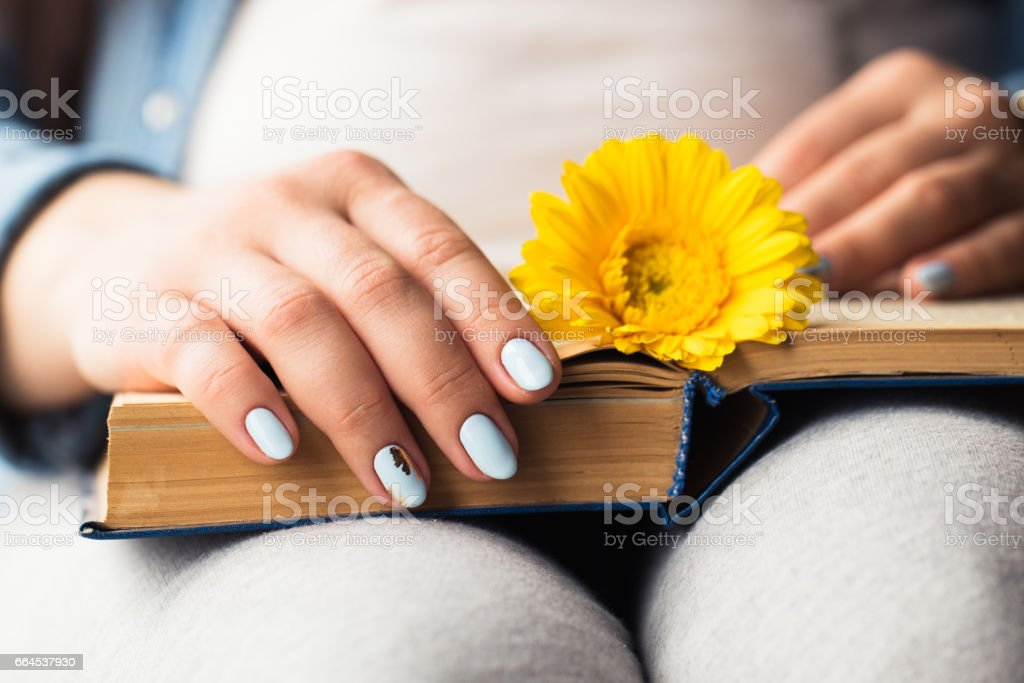 Girl's hands on a book with a yellow flower royalty-free stock photo