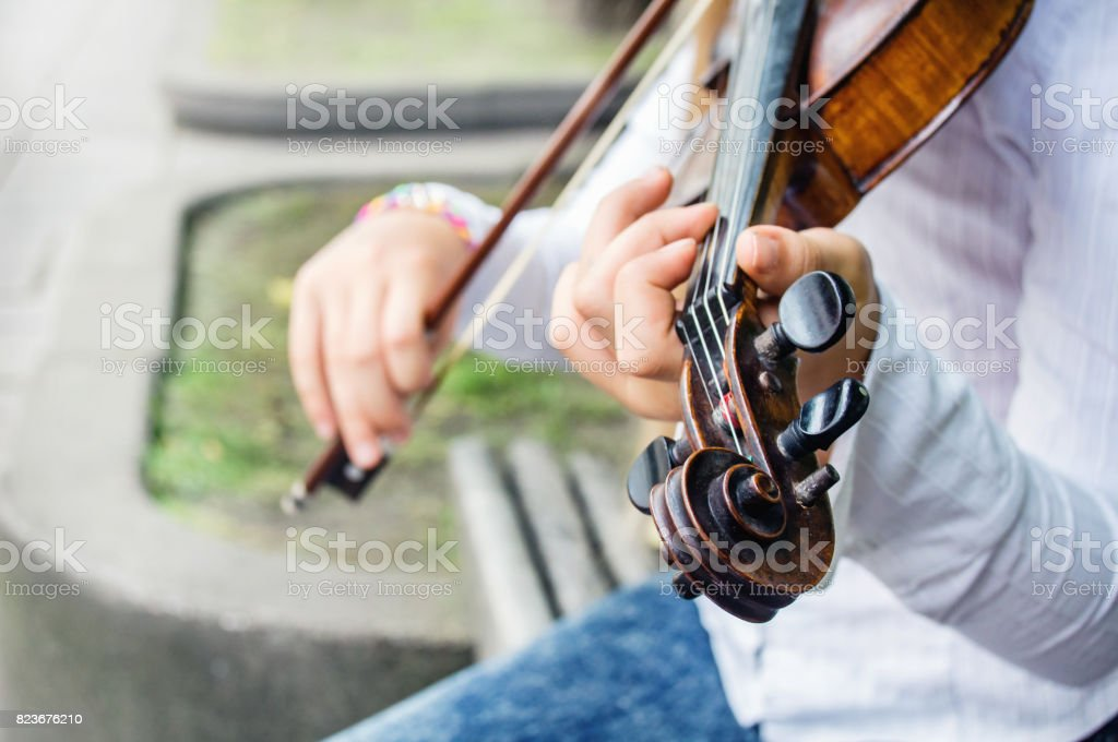 Girl's hands on a violin strings and violin scroll with pegs. stock photo