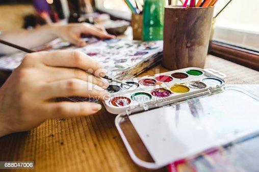 istock Girls hands with brush painting 688047006