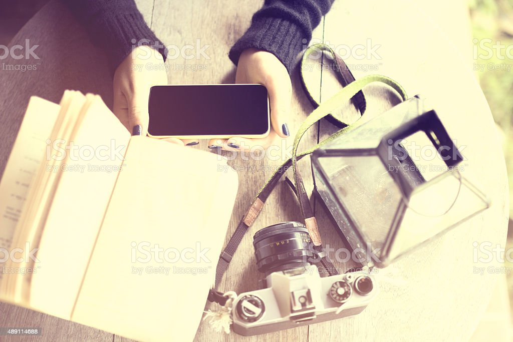 Girl's hands with cell phone, old camera and a book stock photo