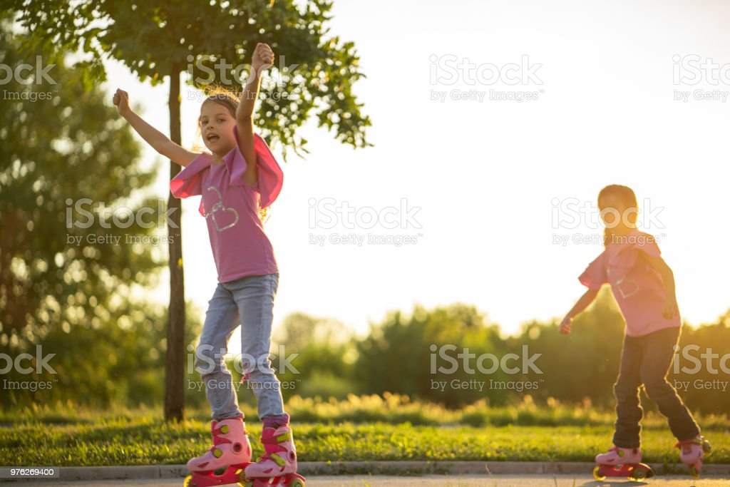 Girls have contest in park on roller skates stock photo