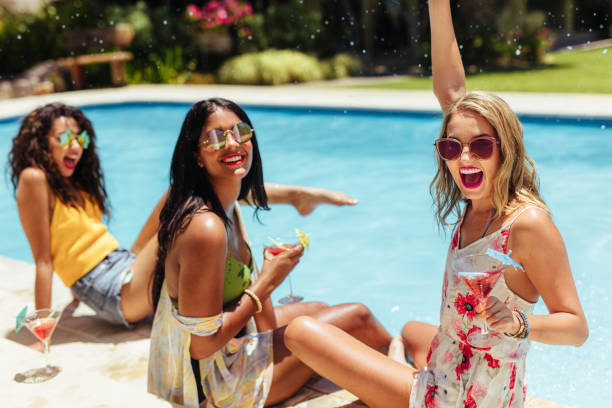 Girls having a party at poolside Party at swimming pool. Group of cheerful girls at the edge of the swimming pool drinking cocktails and laughing. poolside stock pictures, royalty-free photos & images