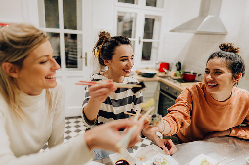 Photo of a group of friends eating traditional Japanese food in the kitchen and having a great time; enjoying in each other's company during dinner at home.