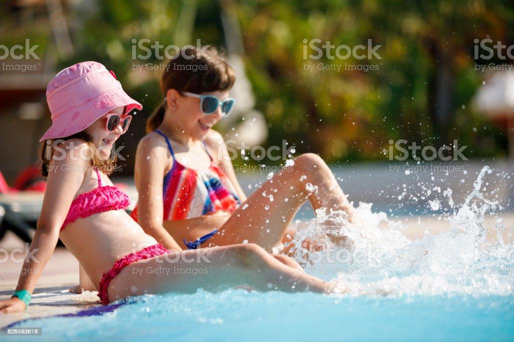 Girls having fun in a swimming pool stock photo