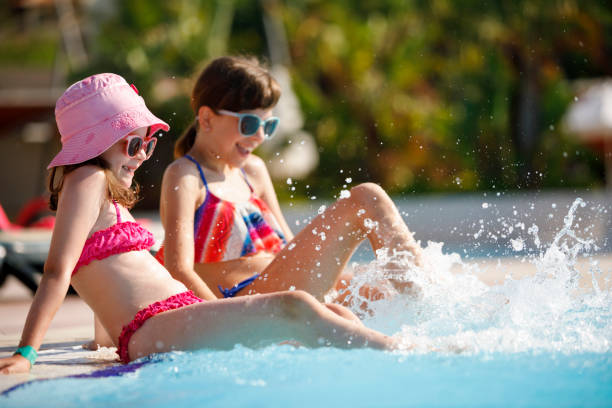 Girls having fun in a swimming pool stock photo