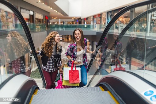 Young women in the shopping mall using the escalator to move on the upper floor