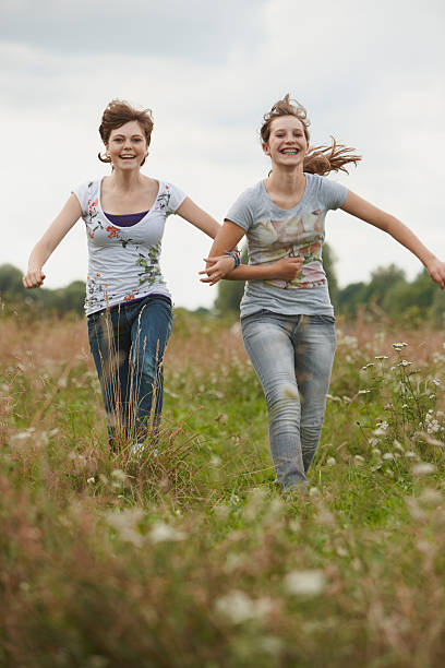 2 girls having fun together in a park stock photo