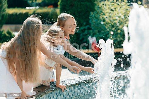 Girls having fun with their mother near fountain
