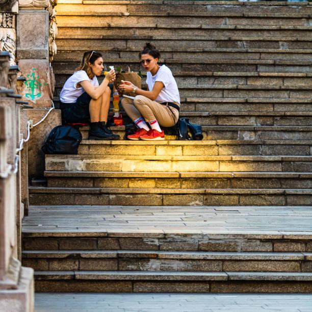 Mädchen beim Mittagessen auf der Treppe in der Altstadt in Bukarest, Rumänien, 2019 – Foto