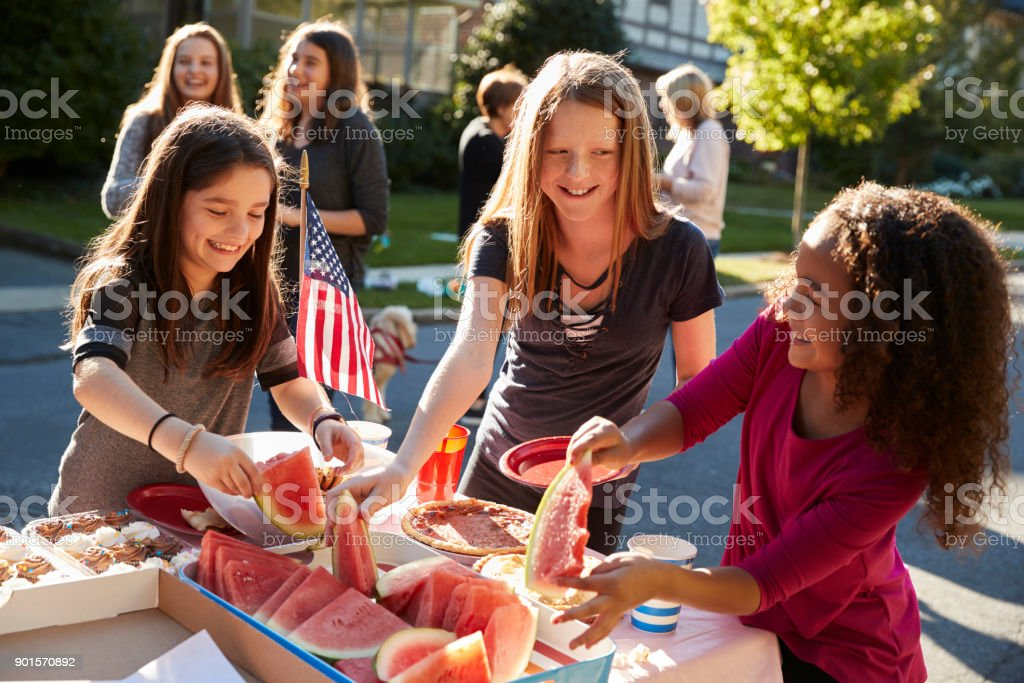 Girls helping themselves to watermelon at a block party stock photo