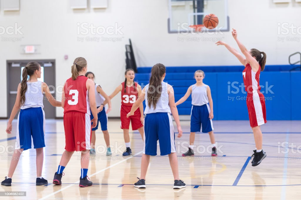A player shoots a free throw during a girl\'s high school basketball...