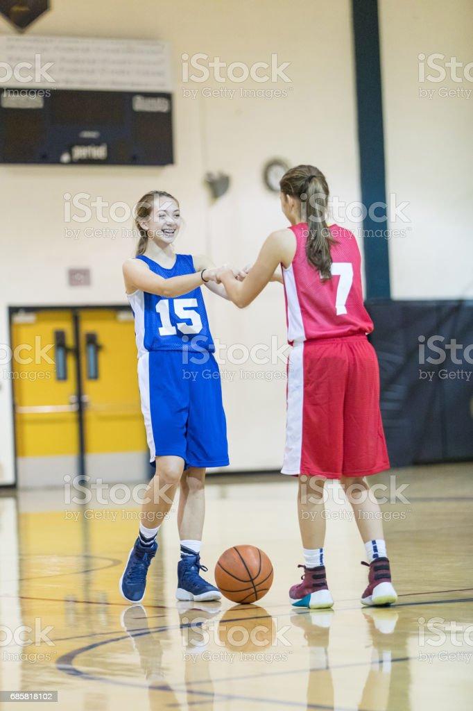 Girls high school basketball game - two players congratulate each...