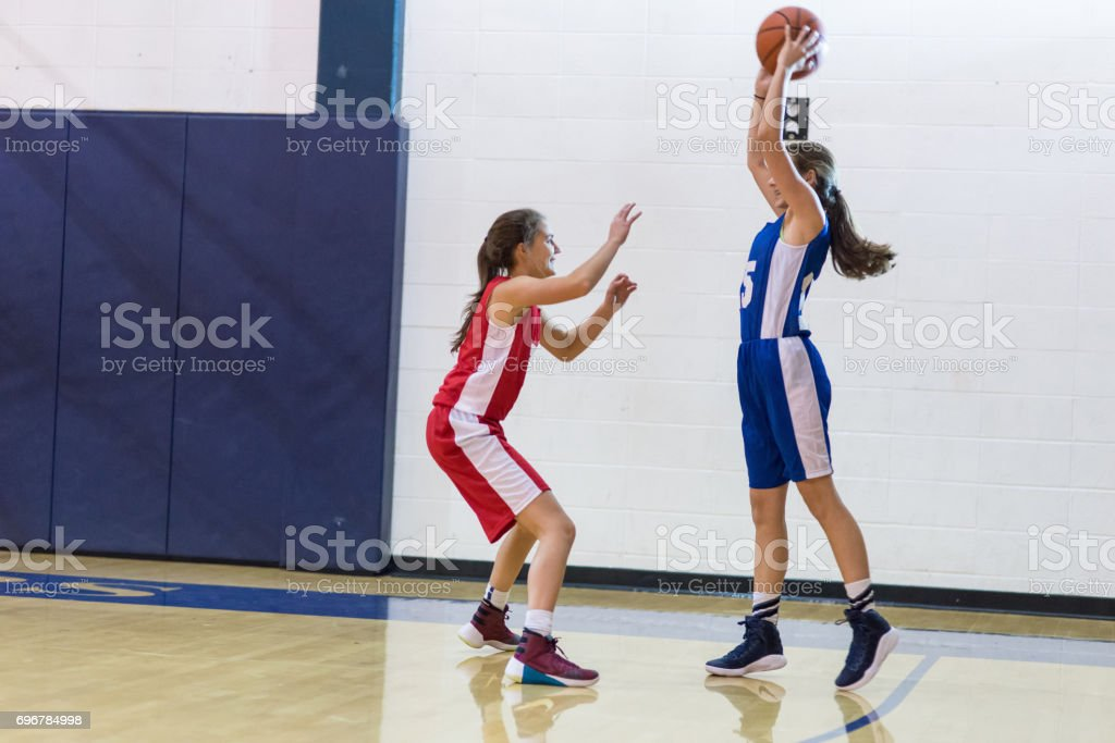 Player holds the ball out by three point line and prepares to pass to...