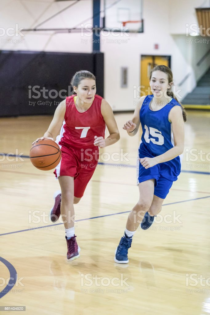 Female high school athletes compete in a basketball game. They are...