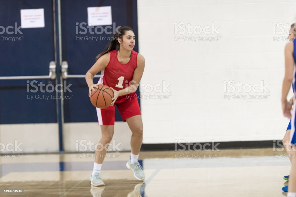 A player holds the ball outside the three point line and tries to...