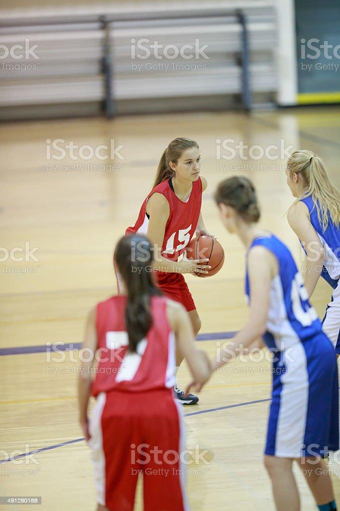 Teenage girls playing high school basketball in uniforms