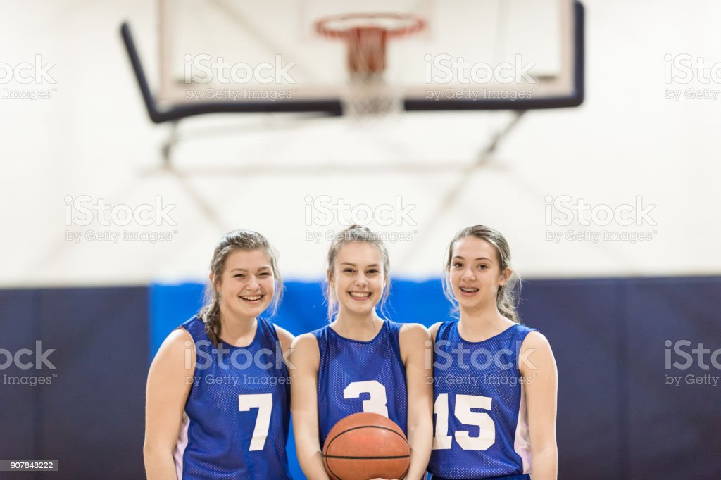 Portrait of three high school basketball players. The girl in the...