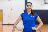 High school player poses with volleyball in gym before her game