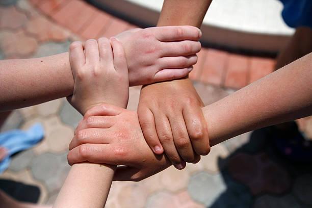 Girls hold hands stock photo