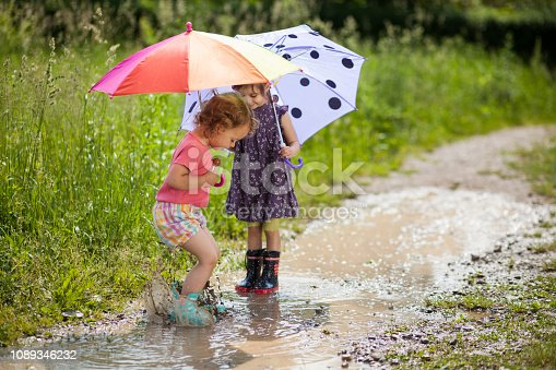 Girls holding umbrellas and lollipop while playing in muddy water.