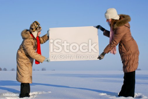 istock Girls holding white poster at winter snowy field 120033389