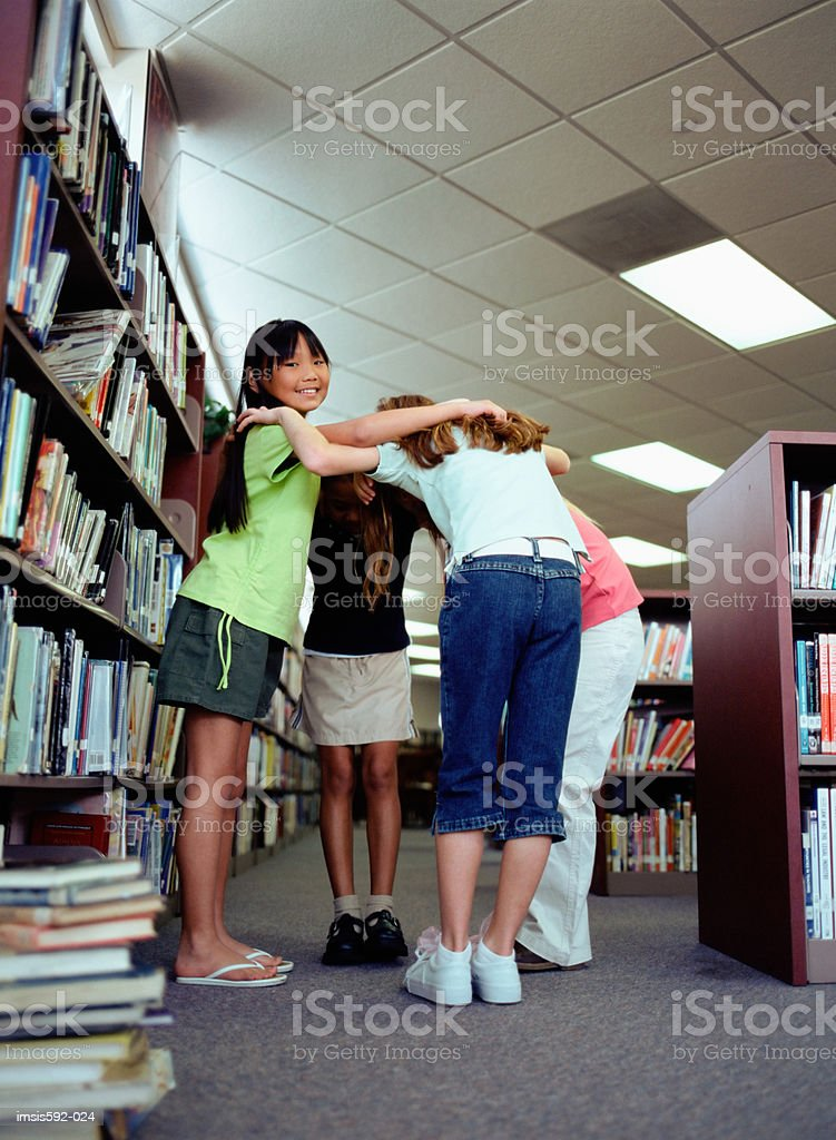 Girls hugging in library royalty free stockfoto