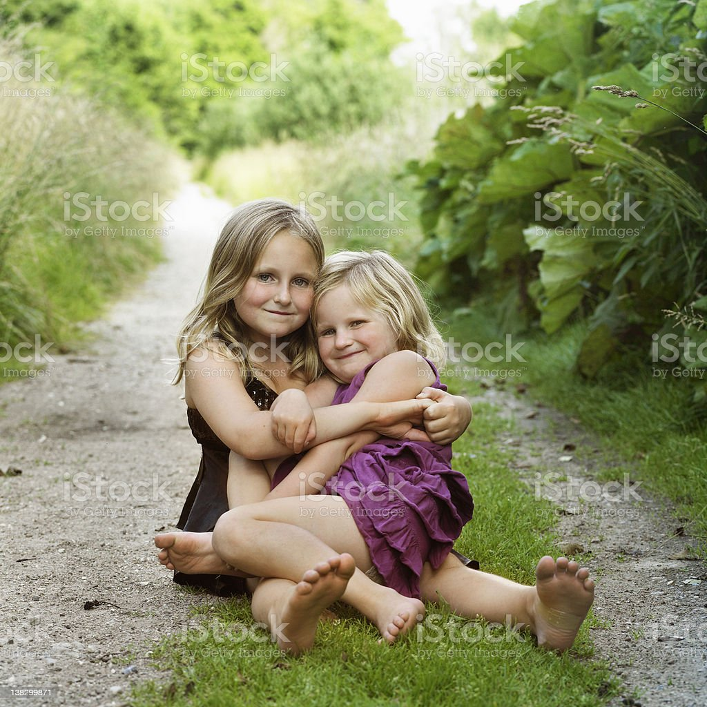 Girls hugging on dirt path stock photo