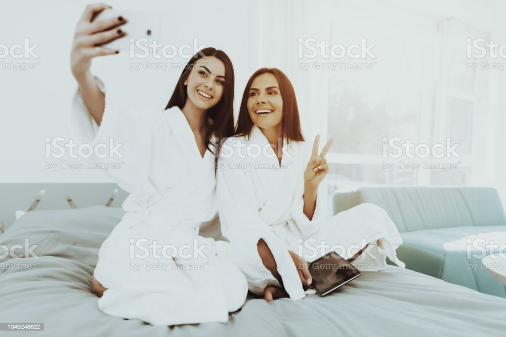 Girls In A Bathrobes Are Doing A Selfie On A Bed. stock photo