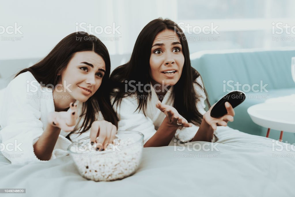 Girls In A Bathrobes Are Watching Movie On Bed. stock photo