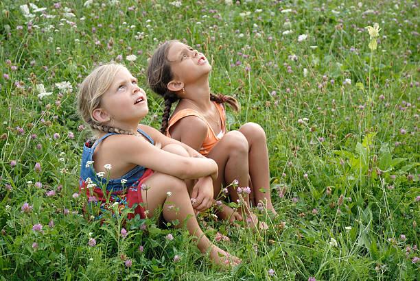 ガールズの花開く草地 ストックフォト