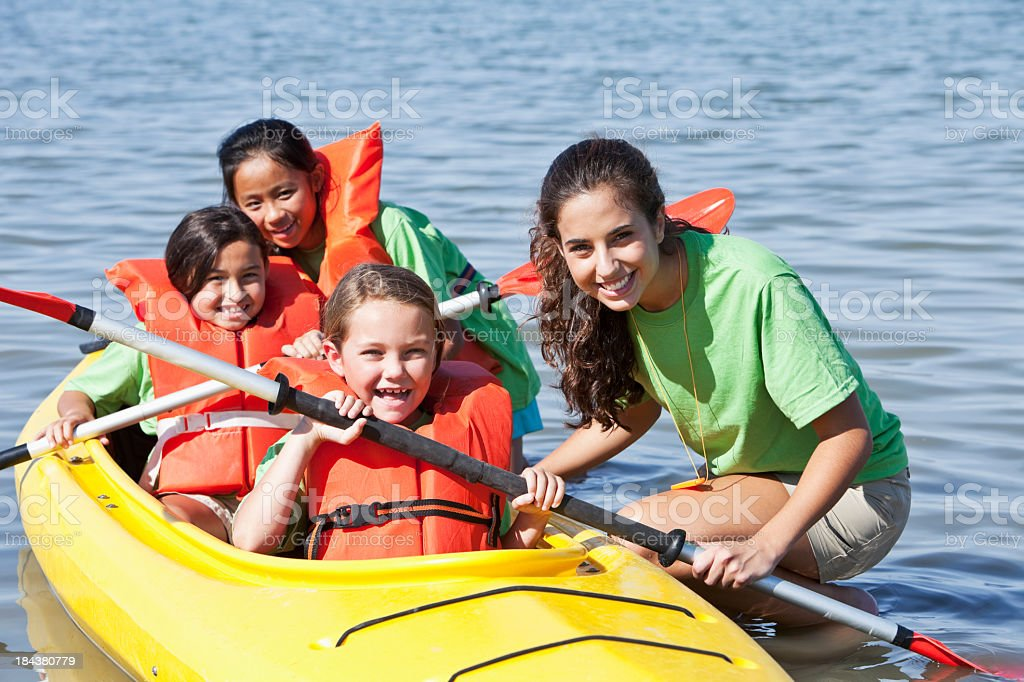 Girls in a double kayak at summer camp stock photo