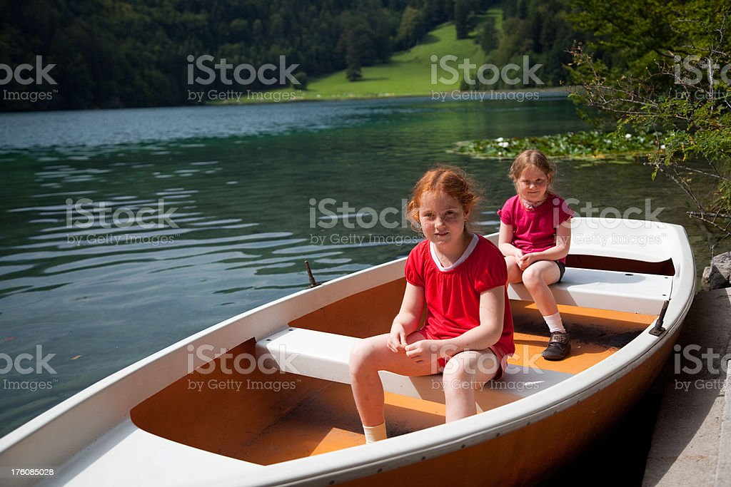 Girls in a rowboat at the lake royalty-free stock photo