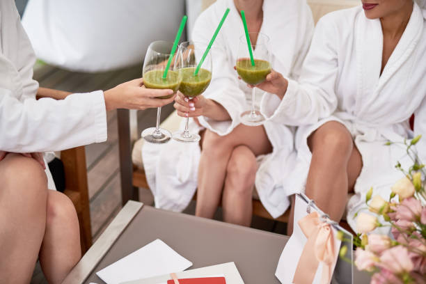 Girls in bathrobes holding drinks and toasting stock photo