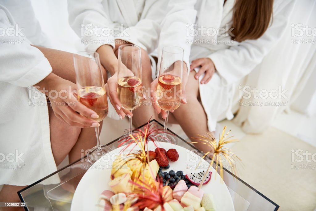 Girls in bathrobes holding glasses of champagne with strawberries stock photo