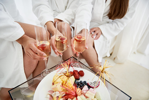 Taste this. Table with sweets and alcohol drinks in women hands. White plate with berries and marshmallows
