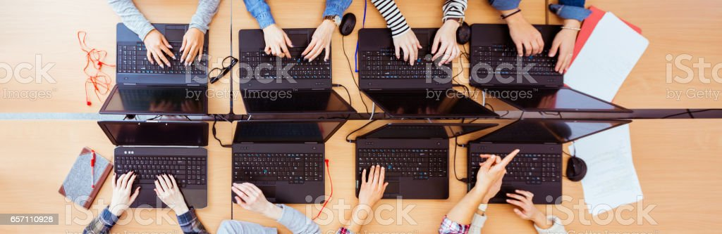Girls in computer lab coding on laptops royalty-free stock photo