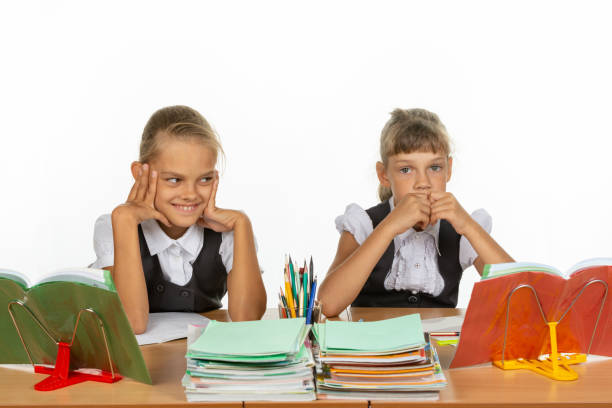Girls in different emotions think about something while sitting at a desk at school Girls in different emotions think about something while sitting at a desk at school antipode stock pictures, royalty-free photos & images