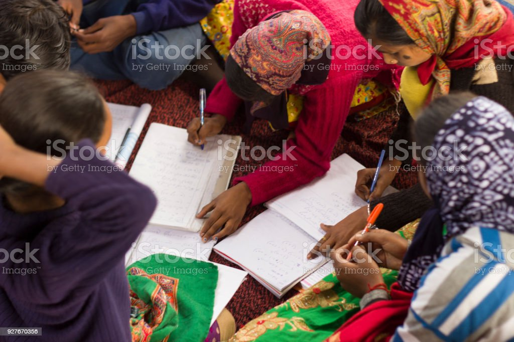 Girls in Indian village school study in a cirlcle, wearing head scarves stock photo