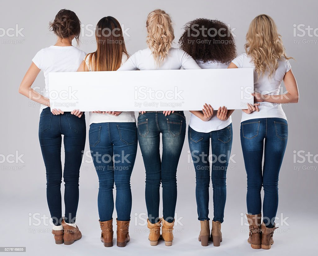 Girls in jeans holding empty banner stock photo