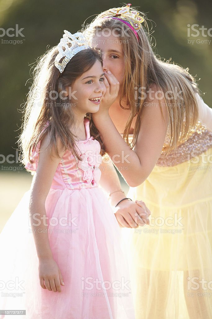 Girls in party dresses whispering royalty-free stock photo