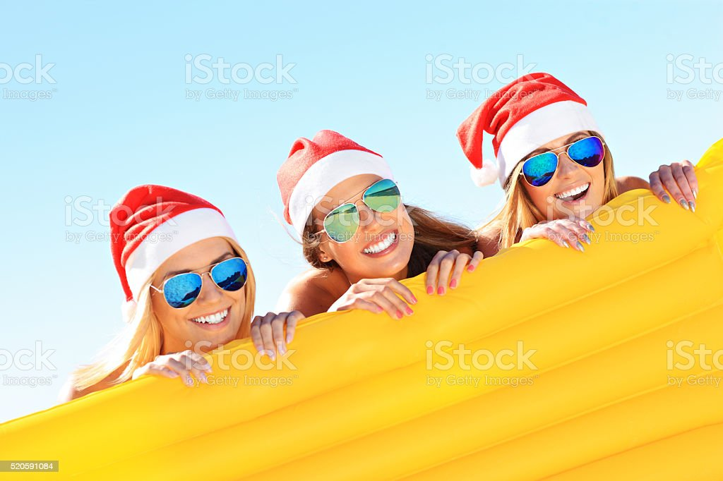 Girls in Santa's hats having fun on the beach stock photo