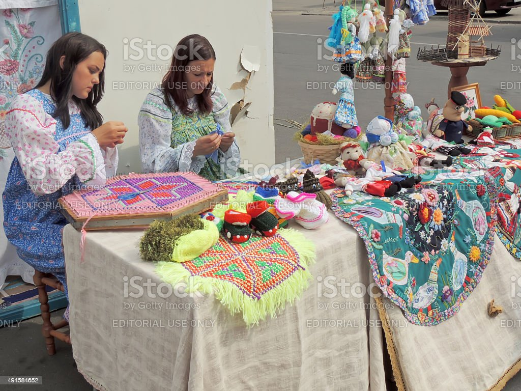 Girls in sarafans busy with embroidery stock photo