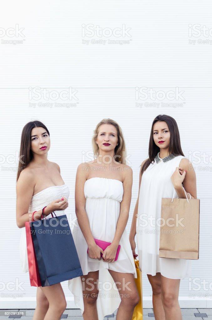 Girls in shopping posing on white wall stock photo