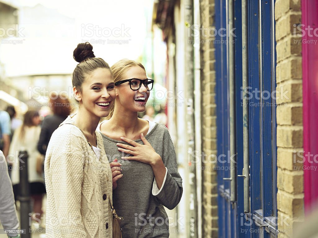 Girls in the city Female friends standing at a shopwindow, having fun. 20-24 Years Stock Photo